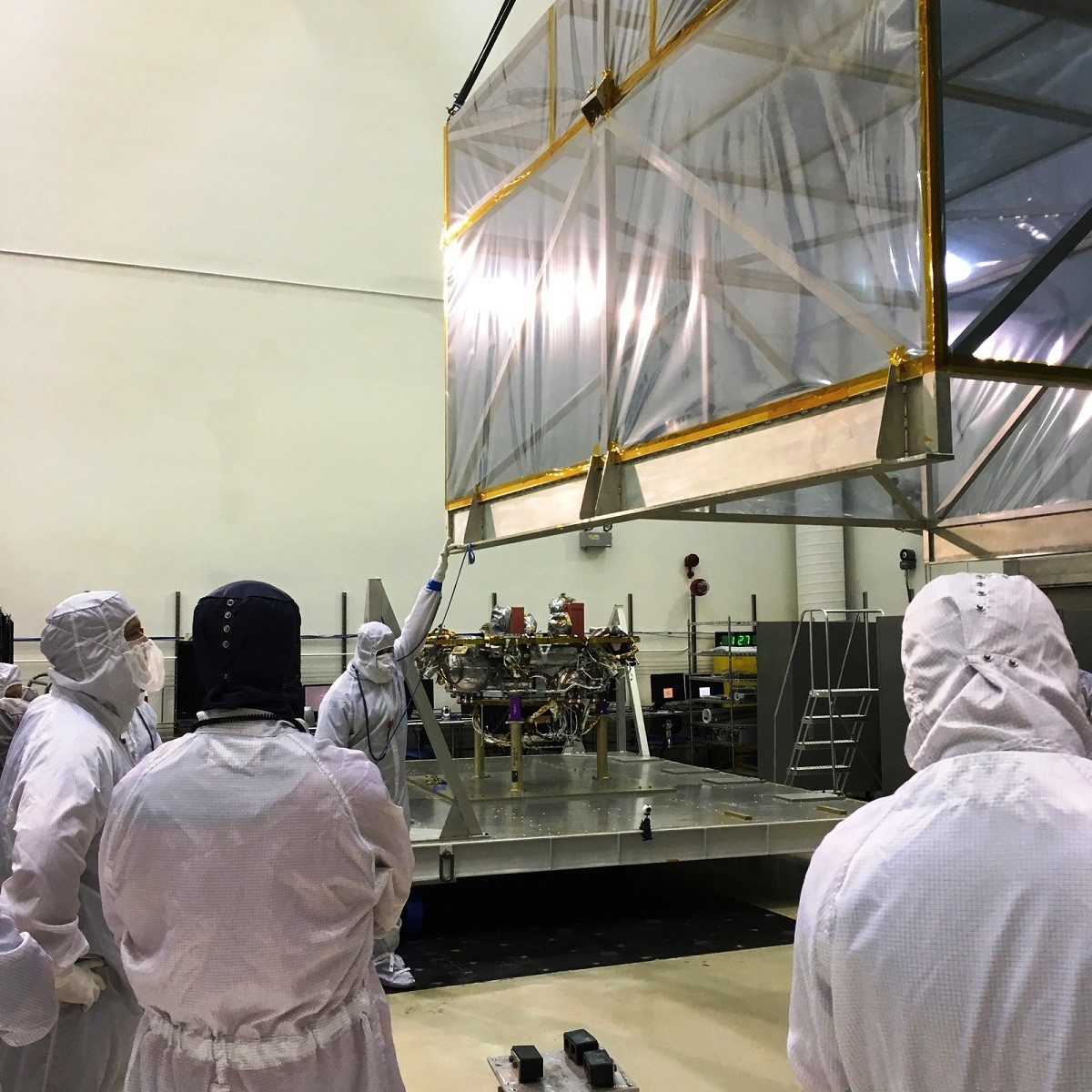 Two JPL engineers are standing next to three different generation vehicles from Mars Rovers